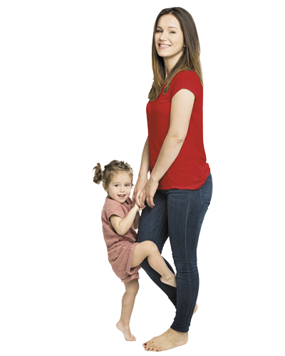 Baby girl (6-9 months) standing on rug, holding onto mother's legs